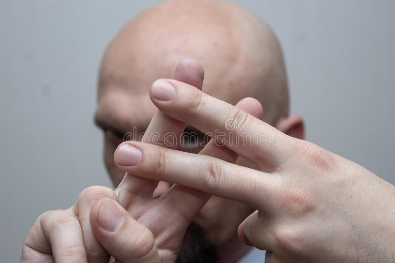 Bald man in a suit shows fingers. Lattice sign, hashtag, musical sharp stock images