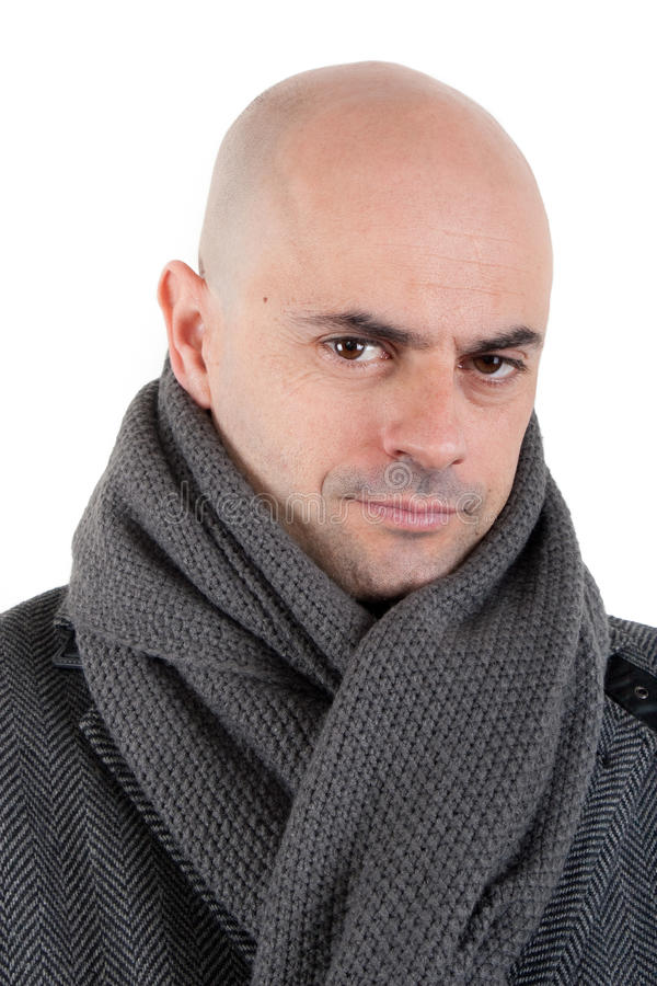 Bald man in tweed coat and scarf. Portrait of a bald man in tweed coat and grey scarf loking at camera with half smile. Isolated stock photo
