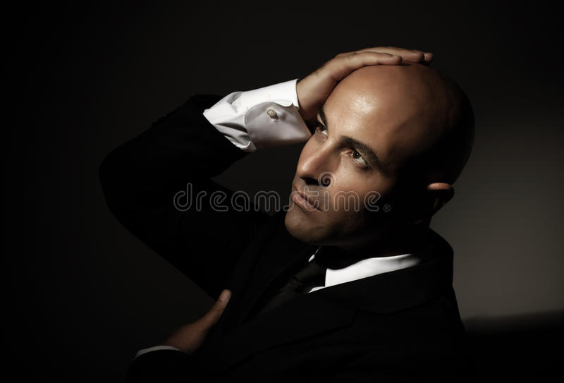 Bald man wearing black suit. Attractive bald arabian man wearing formal black suit, festive dresscode, mens fashion, executive manager stock photography