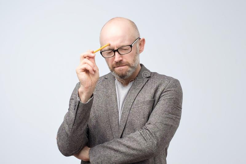 Bald mature european man is thinking about something with pencil. How to solve this problem royalty free stock images