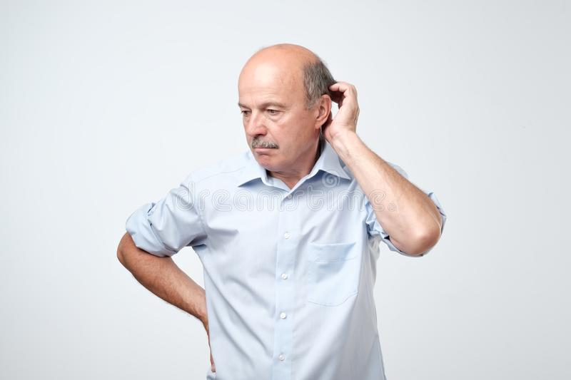 Bald mature man with mustache in blue shirt is suffering from indecision. royalty free stock photos