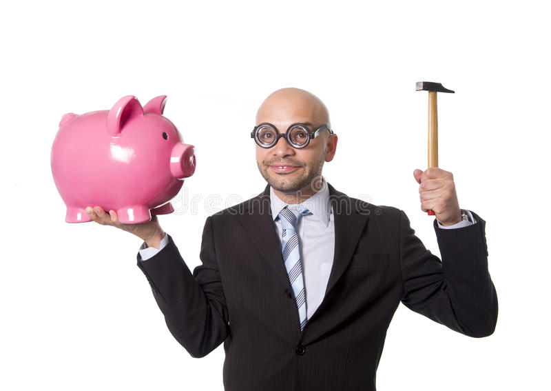 Bald nerdy businessman with geek glasses holding pink piggybank on his hand ready to break piggy bank with hammer. And take money out isolated on white royalty free stock photos