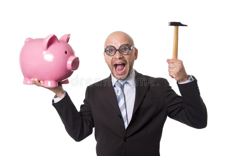 Bald nerdy businessman with geek glasses holding pink piggybank on his hand ready to break piggy bank with hammer. And take money out isolated on white stock image