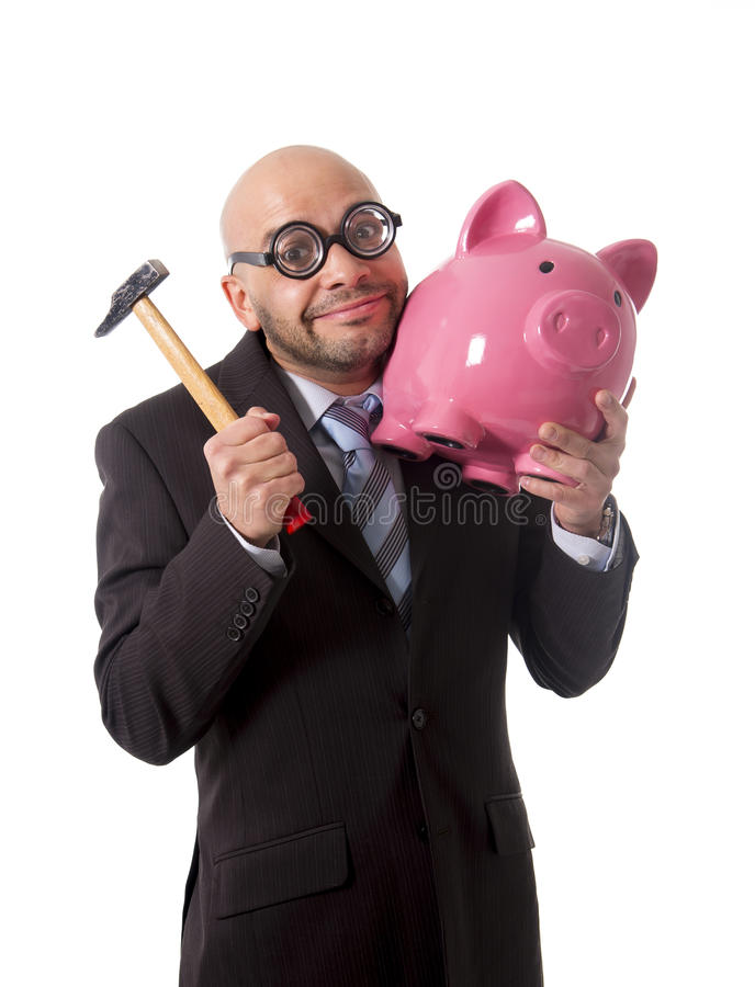 Bald nerdy businessman with geek glasses holding pink piggybank on his hand ready to break piggy bank with hammer. And take money out isolated on white stock images