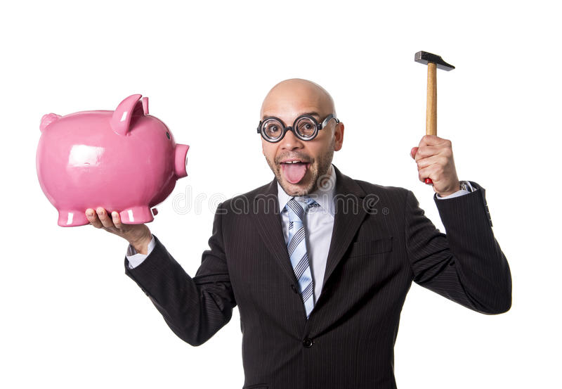 Bald nerdy businessman with geek glasses holding pink piggybank on his hand ready to break piggy bank with hammer. And take money out isolated on white royalty free stock image