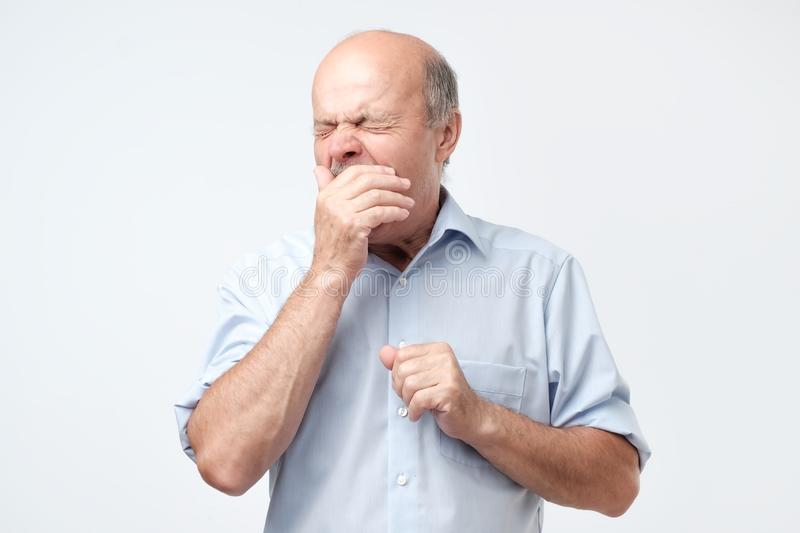Bald retired man feels sleepy, yawns as feels tired, opens mouth widely royalty free stock photos