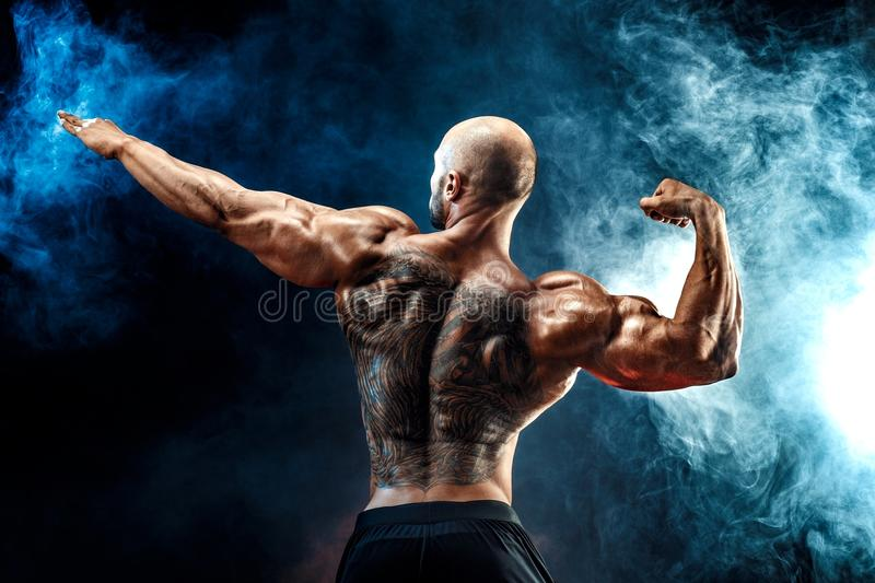 Back view of tattoed muscular man posing with arm up royalty free stock photo