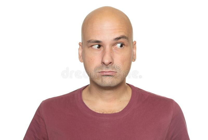 Bald 40 years man is looking aside. Isolated stock image