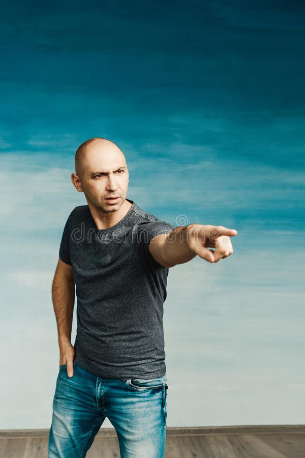 A bald young man in a gray T-shirt and jeans is smiling and pointing with a finger at the side on a blue background. stock photography