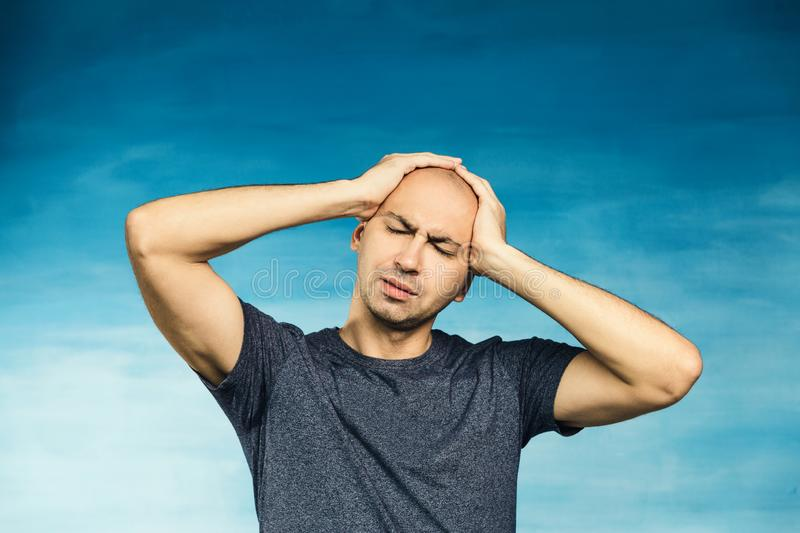 A bald young man in a gray T-shirt twisted her sad face in pain and raises his hands to her face stock photo