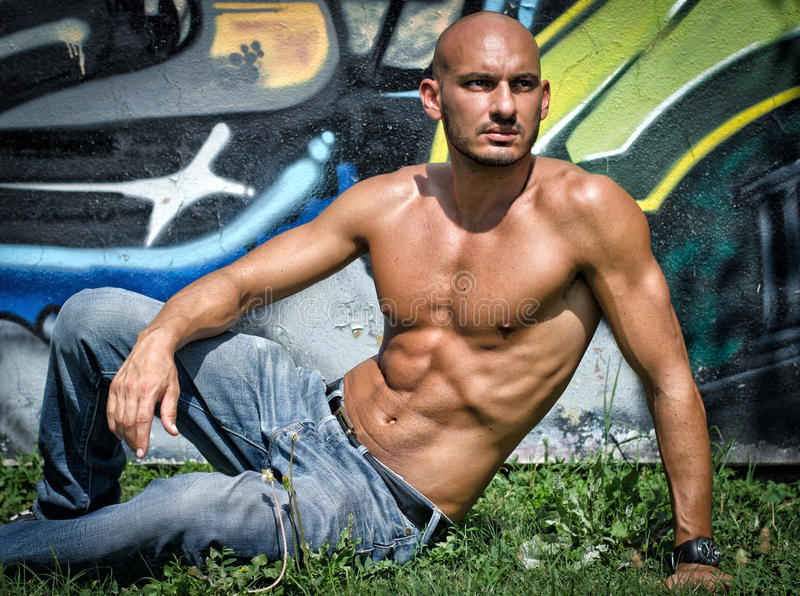 Bald young man shirtless outdoors sitting. In front of graffiti wall on grass royalty free stock image