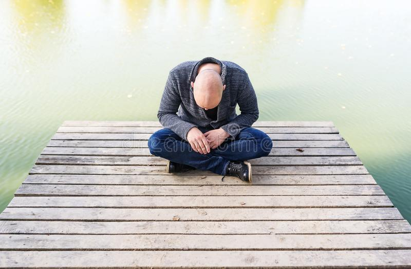 Bald young man sitting on the pier in the park and meditating royalty free stock photo