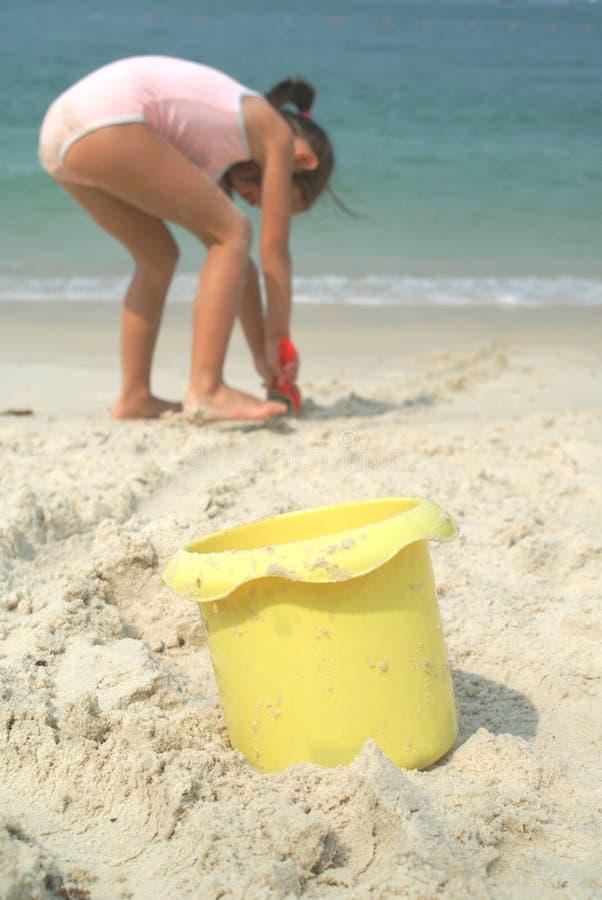 Balde amarelo com a menina na praia fotografia de stock