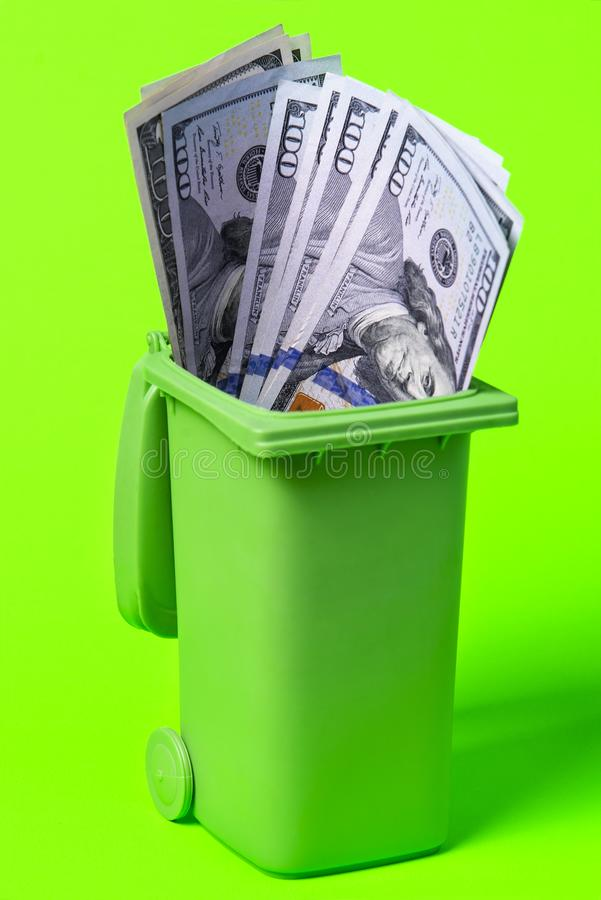 Balde do lixo do dinheiro isolado no fundo verde fotografia de stock
