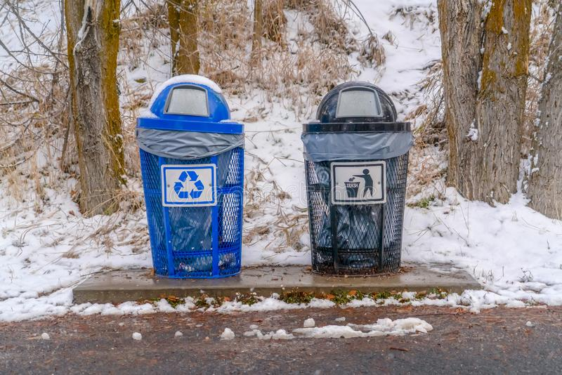 Baldes do lixo com fundo nevado da inclinação e das árvores fotos de stock