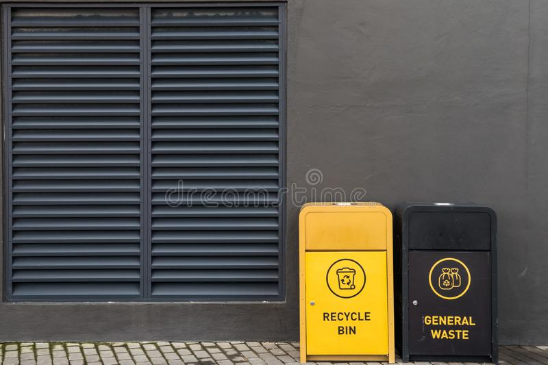 Baldes do lixo contra a parede escura na área urbana imagem de stock