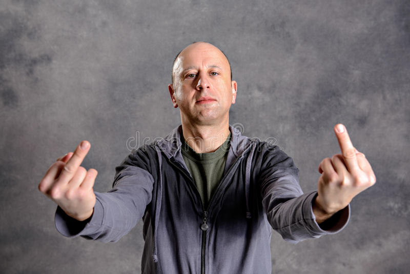 Baldheaded man showing middle finger stock image
