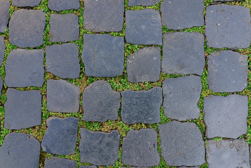Baldosa antigua de la piedra del granito con la hierba verde como fondo imágenes de archivo libres de regalías