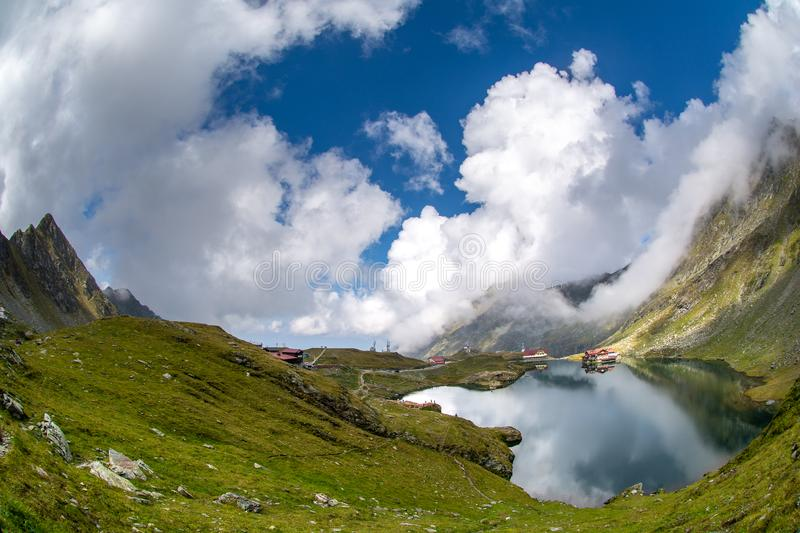 Balea glacier lake, Transfagarasan road in Romania Carpathian Fagaras mountains. With clouds and clear sky royalty free stock image