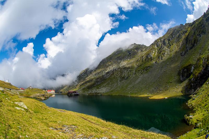 Balea glacier lake, Transfagarasan road in Romania Carpathian Fagaras mountains. With clouds and clear sky stock image
