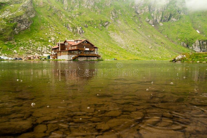 Balea lake with lakehouse on a rainy day stock photo