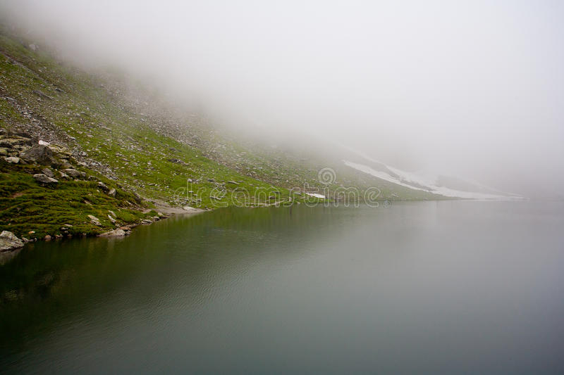 Balea Lake in Romania under a blanket of clouds. Landscape of Balea Lake in Romania in a misty day royalty free stock image