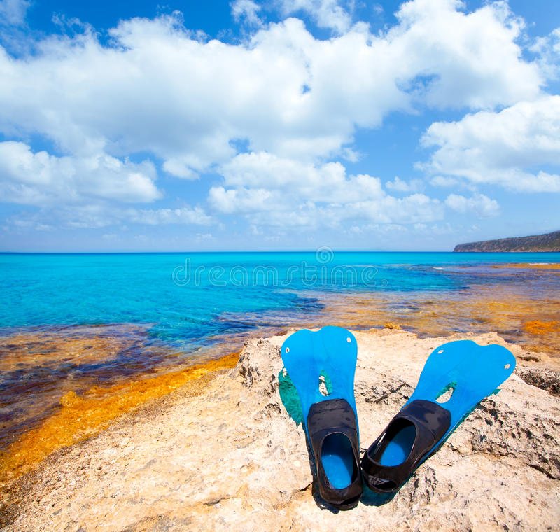 Balearic Formentera island with scuba diving fins. Balearic Formentera island with scuba diving blue fins on a rock stock photography