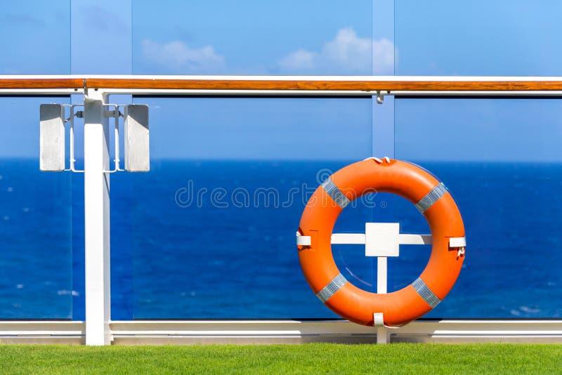 Baleeira de laranja num convés de cruzeiro com oceano sobre fundo com céu azul e espaço de cópia fotos de stock