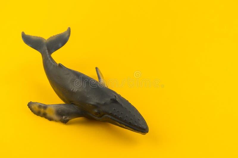 Baleine de jouet de plastique sur un fond jaune photos libres de droits