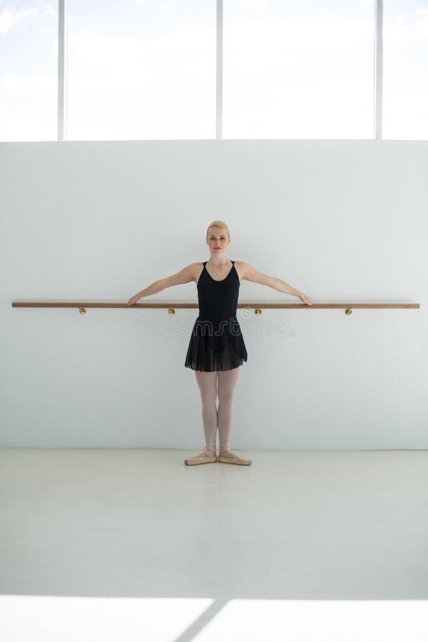 Balerina ćwiczy balet rusza się przy barre fotografia stock