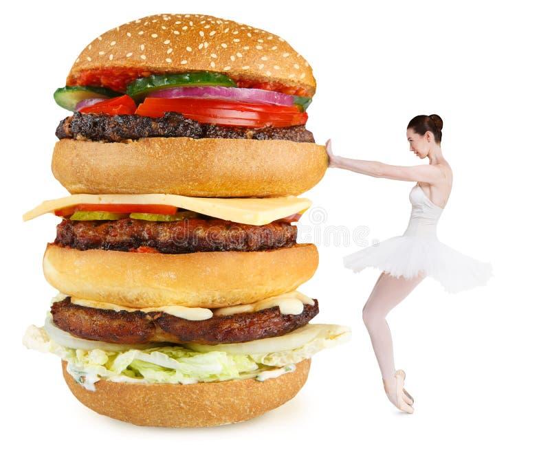 Balerina mince rejetant le grand hamburger pour rester convenable photographie stock