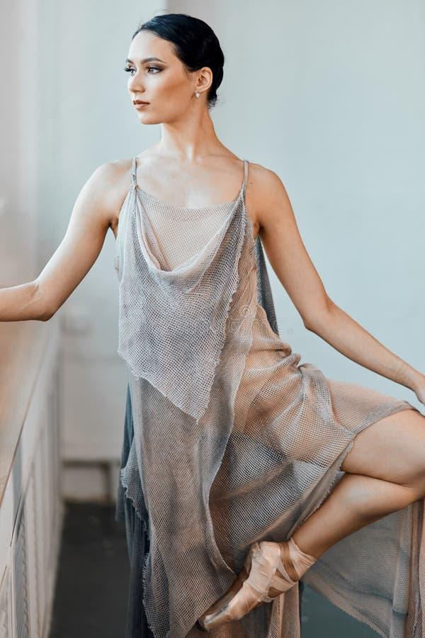 Balerina w eleganckim scenicznym kostiumu grże w górę występu przed, napina stopę zdjęcia stock
