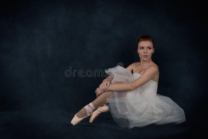 Balerina w pointes i białej sukni siedzi i odpoczynek fotografia stock