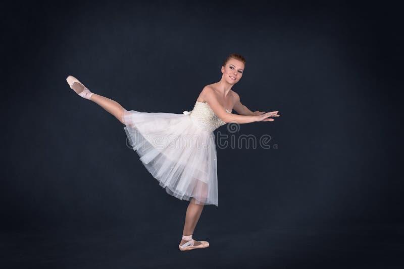 Balerina w pointes i białej sukni tanczy na zmroku z powrotem zdjęcie royalty free