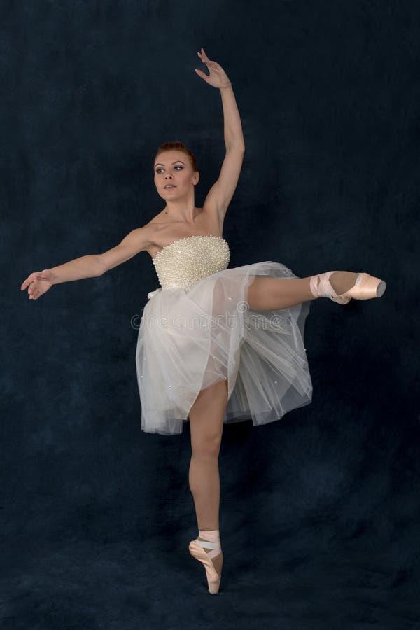 Balerina w pointes i sukni tanczy na ciemnym backgroun fotografia royalty free