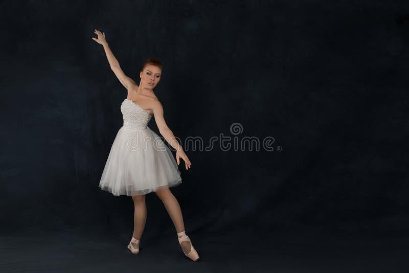 Balerina w pointes i sukni tanczy na ciemnym tle zdjęcie stock