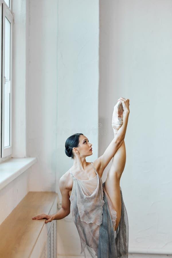 Balerina w sceny sukni rozci?gania nodze w pionowo rozszczepionym pobliskim okno w klasie fotografia stock