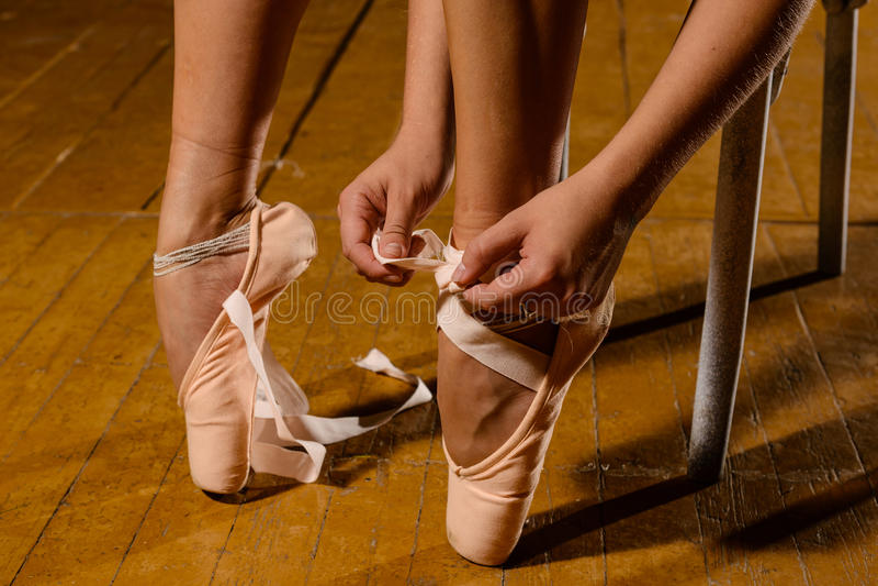 Balerina wiąże pointe baletniczych buty na scenie obrazy stock