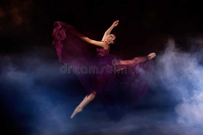 Balerina z długim smokingowym doskakiwaniem na scenie obraz royalty free