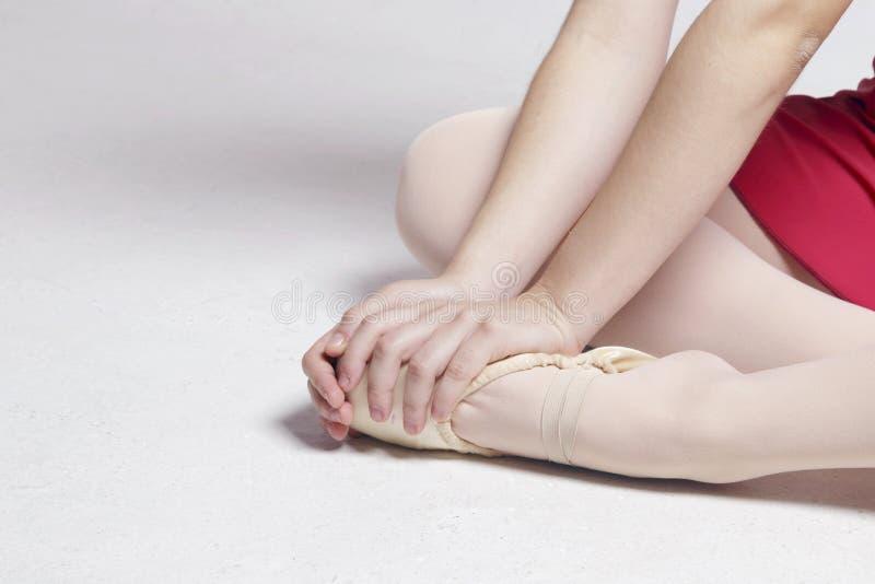 Baleriny obsiadanie na białej podłoga, dotyka jej stopę zdjęcie royalty free