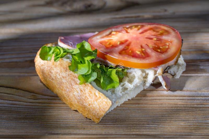 Baleron, sa?ata i pomidorowa kanapka na drewnianym tle iluminuj?cym nier zdjęcie royalty free