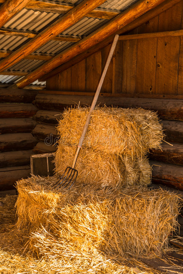 Bales Of Straw Hay With Pitchfork In Barn Stock Image