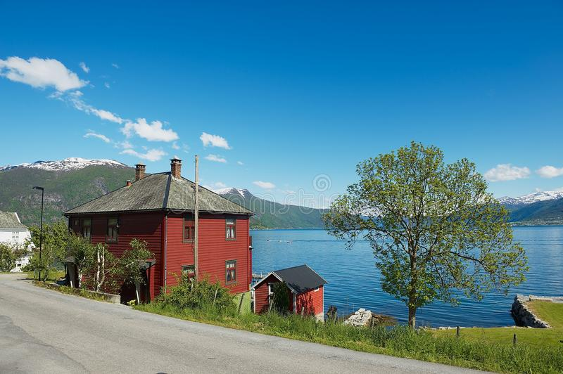 Traditional red painted Norwegian house with Sognefjord at the background in Balestrand, Norway. BALESTRAND, NORWAY - JUNE 06, 2012: View to the traditional red royalty free stock image