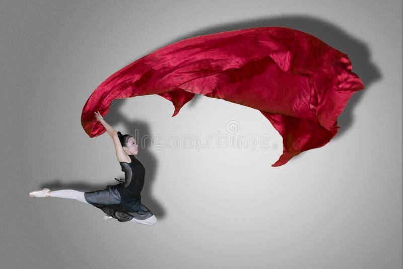 Baletniczego tancerza doskakiwanie z tkaniną na studiu obrazy royalty free
