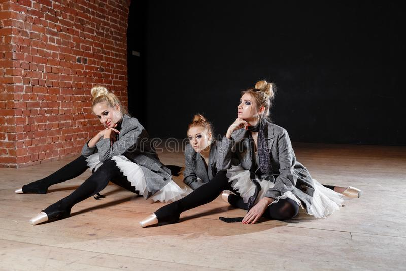 Baletniczy pojęcie Młode balerin dziewczyny relaksują obsiadanie na podłoga Kobiety przy próbą w białej spódniczce baletnicy i po obraz royalty free