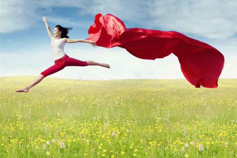Baletniczy tancerz skacze z tkaniną przy polem zdjęcia stock