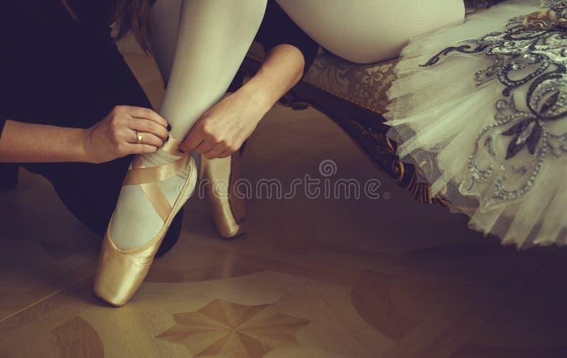 Baletniczy tancerz wiąże baletniczych buty Zakończenie zdjęcie stock