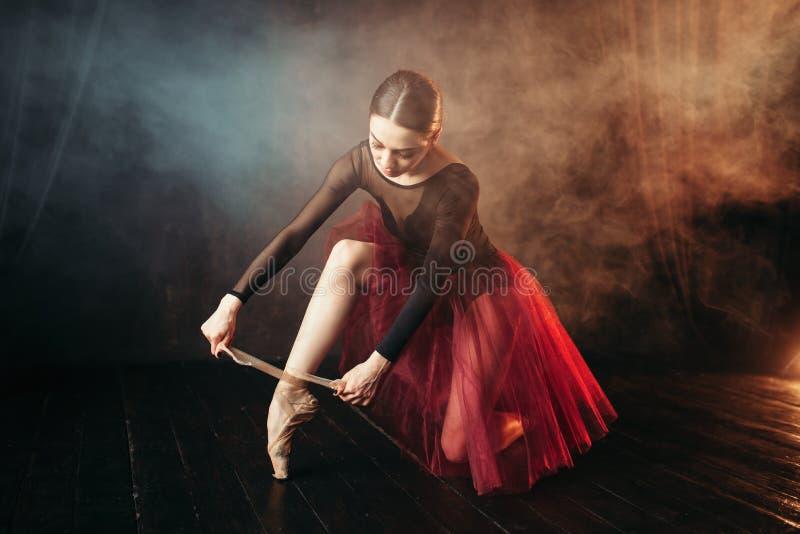 Baletniczy tancerz wiąże pointe buty zdjęcie stock