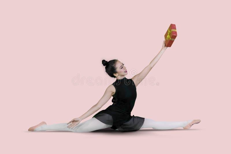 Baletniczy tancerz z prezenta pudełkiem robi rozszczepionemu ćwiczeniu obraz stock