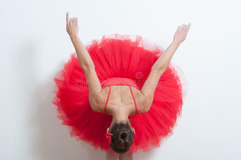 Balettdansör i rött visa hennes baksida royaltyfri fotografi